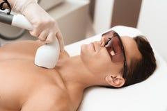 Mannen kom till tillvägagångssättet av laser-hårborttagning Doktorn behandlar hans hals och framsida med en special apparatur royaltyfri fotografi