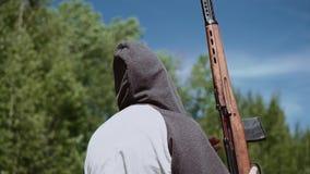Mannen kommer med ett prickskyttgevär i hans händer Efter någon tid vilar geväret på skuldran arkivfilmer