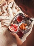 Mannen kommer med frukosten i säng Royaltyfri Fotografi