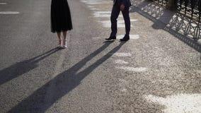 Mannen kommer till den unga kvinnan på en gata Koppla ihop att omfamna på deras datum i en stadsgata på ottan, skuggor på a arkivfilmer