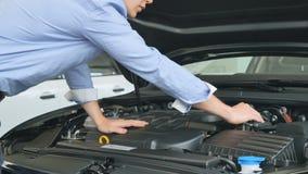 Mannen kontrollerar bilen under huven i bilåterförsäljare arkivfilmer