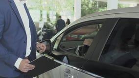 Mannen kontrollerar kabinen och representanten för bil` som s talar omkring auto i bilvisningslokal lager videofilmer