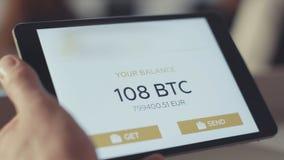Mannen kontrollerar kontot på minnestavlan materiel Kontrollera bitcoinjämvikten på kontot royaltyfria bilder
