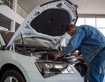 Mannen kontrollerar motorrummet av den nya bilen Royaltyfria Bilder