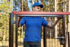 Mannen kontrollerar nivån av nya staketportar fotografering för bildbyråer