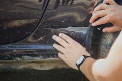 Mannen kontrollerar skada för bil t arkivbild
