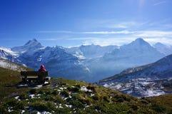 Mannen kopplar av att vila på placering, når han har klättrat snömoutainintelligensen royaltyfria foton