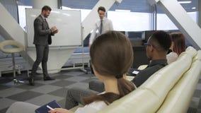 Mannen korrigerar mistkesna av hans kollega på presentationen i det moderna kontoret arkivfilmer