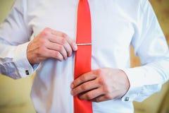 Mannen korrigerar slipshållarecloseupen arkivbild