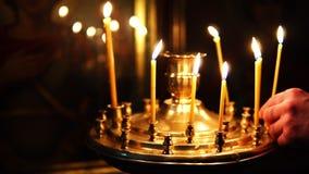 Mannen korrigerar stearinljus som bränner i ljusstaken för den heliga framsidan i Christian Church stock video