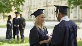 Mannen kvinnlig avlägger examen samtal efter ceremoni, universitetutbildning, vuxet liv lager videofilmer