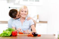 Mannen kysser kvinnan, medan hon lagar mat arkivfoton