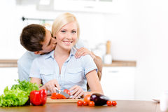 Mannen kysser kvinnlign, medan hon lagar mat royaltyfri foto