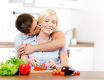 Mannen kysser unga flickan, medan hon lagar mat royaltyfri fotografi