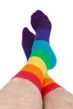 Mannen lägger benen på ryggen i isolerade färgrika roliga sockor - arkivfoton