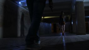 Mannen lägger benen på ryggen med kniven som jagar kvinnan i tunnel stock video