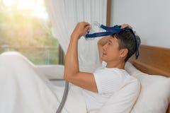 Mannen lägger i säng som bär CPAP-maskeringen, terapi för sömnapnea royaltyfri bild