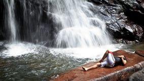 Mannen lägger längst ner av en vattenfall för att kyla av, Malaysia royaltyfri fotografi