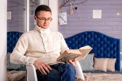 Mannen läser bokjulpyntet Royaltyfri Foto