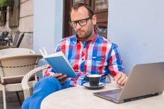 Mannen läser en bok i kafé. Han dricker kaffe. Fotografering för Bildbyråer