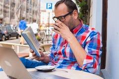 Mannen läser en bok i kafé. Han dricker kaffe. Arkivfoton