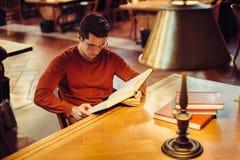 Mannen läser en bok som gör studieforskning som sitter på offentligt bibliotektabellen royaltyfri bild