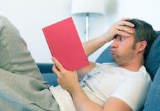 Mannen läser en röd bok royaltyfria bilder