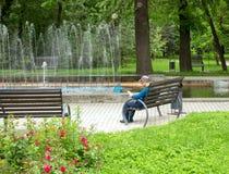 Mannen läser en tidning på en bänk nära springbrunnen royaltyfria bilder