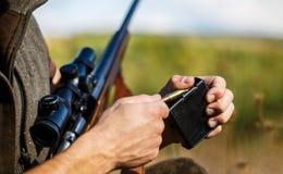 Mannen laddar ett jaktgev?r Manlig j?gare i klart att jaga closeup Ammunitionar med ett vapen, kassetter J?gareman royaltyfri foto