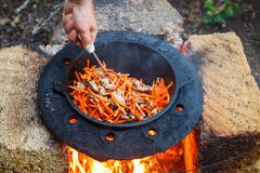 Mannen lagar mat nationell pilaff i en kittel utomhus arkivbild