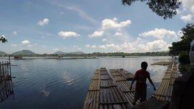 Mannen landsätter från bambuflotten bredvid van vid bambupoler underhåller fiskburar stock video