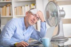 Mannen lider från värme i kontoret eller hemma Royaltyfri Foto