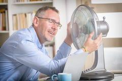Mannen lider från värme i kontoret eller hemma Royaltyfria Bilder