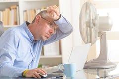 Mannen lider från värme i kontoret eller hemma Arkivbild