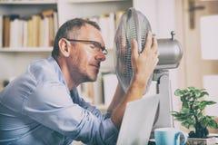 Mannen lider från värme i kontoret eller hemma royaltyfri bild