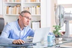 Mannen lider från värme i kontoret eller hemma Fotografering för Bildbyråer