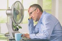 Mannen lider från värme i kontoret eller hemma arkivfoto