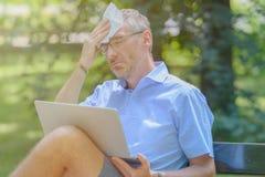 Mannen lider från värme, medan arbeta med bärbara datorn royaltyfria foton