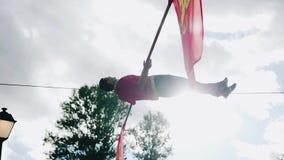 Mannen ligger beautifully på ett rep som sträcks över jordningen lager videofilmer