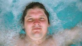 Mannen ligger kopplar av i bubbelpoolen och ser kameran Den Caucasian mannen som vilar i en pöl, ligger på vatten Beskåda lager videofilmer
