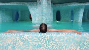 Mannen ligger kopplar av i simbassängen Caucasian man som vilar i bubbelpoolen tillbaka sikt stock video