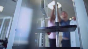 Mannen lyfter vikt med instruktören i idrottshallen Fokus på simulatorn Folk i den sunda livsstilen för idrottshall arkivfilmer