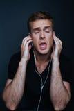 Mannen lyssnar till favorit- musik med den tillbaka v-halsen royaltyfria bilder