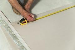 Mannen mäter drywallen Royaltyfri Foto