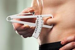 Mannen mäter hans kroppsfett med klämmor Royaltyfri Bild