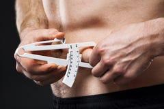 Mannen mäter hans kroppsfett med klämmor royaltyfria foton