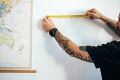Mannen mäter väggen med att mäta bandet fotografering för bildbyråer