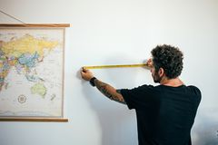 Mannen mäter väggen med att mäta bandet royaltyfria bilder