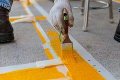 Mannen målar den konkreta vägen Arkivfoto