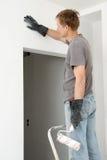 Mannen målar en vägg med en rulle Royaltyfria Bilder